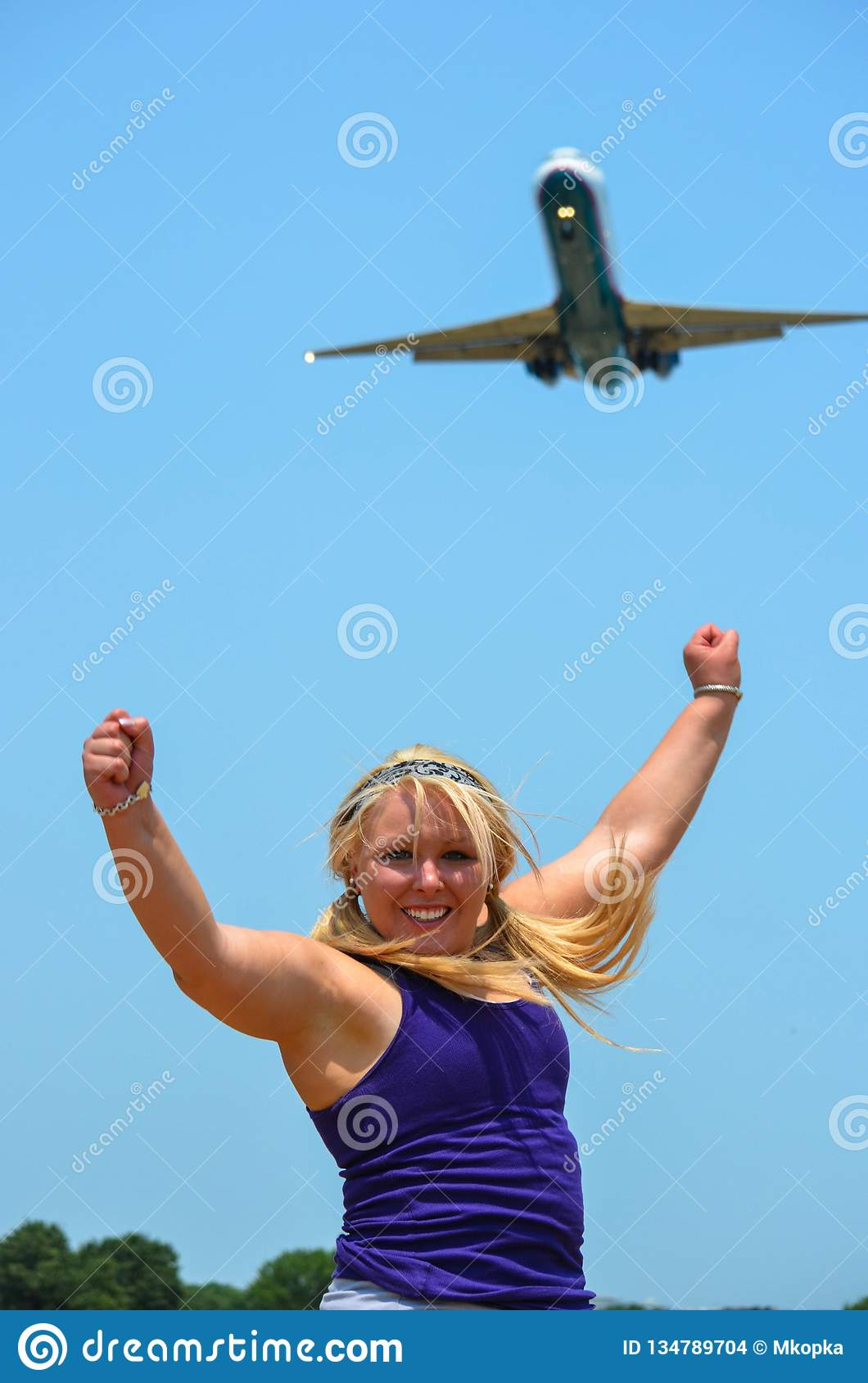 Young adult woman poses with her arms up with a large passenger jet airplane defocused in background. Concept for travel, deals