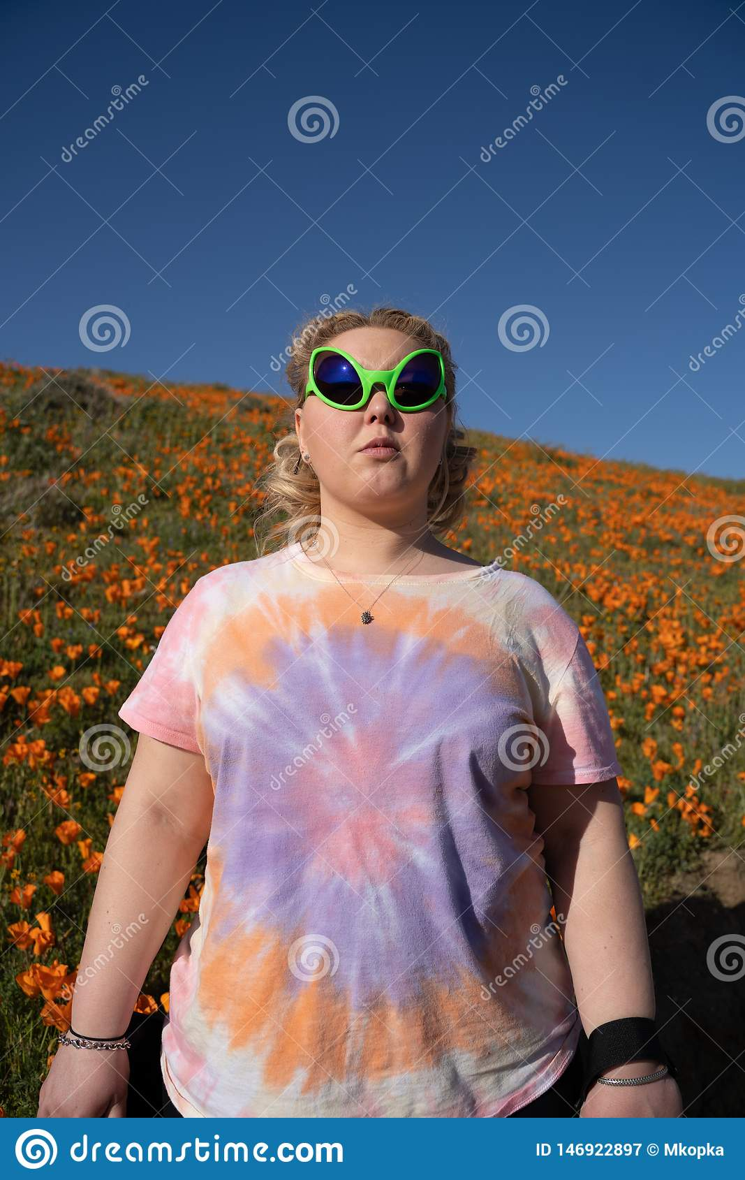 Young adult woman wearing alien sunglasses and a tie dye t-shirt stands in a field of poppies