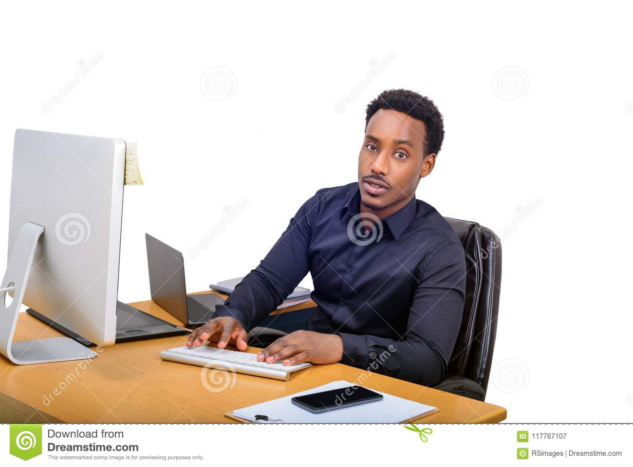 Young African American business man sitting at his office desk and typing on computer