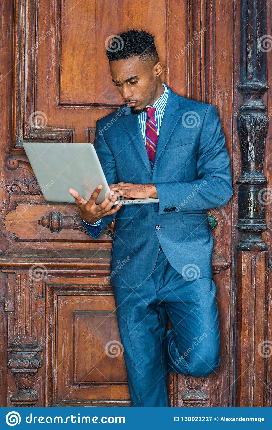 b80fbb95c2 Young African American Businessman with beard working in New York, wearing  sky blue suit, violet red patterned tie, standing by brown vintage office  door, ...