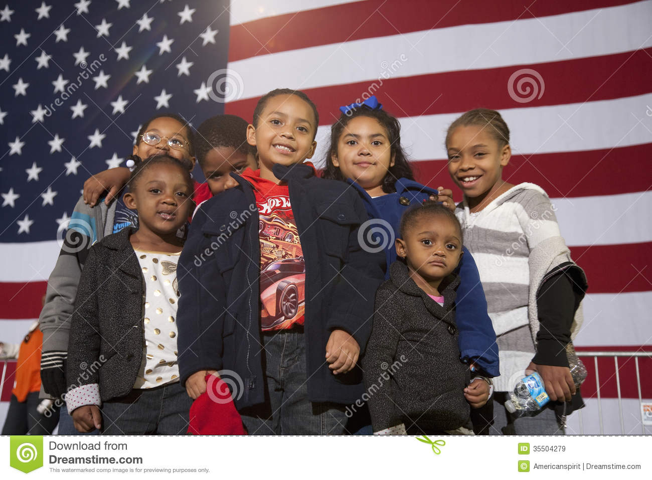 Young African American children stand in front of American Flag