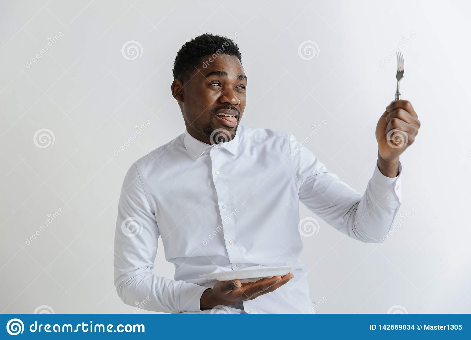 Young african american guy holding empty dish and fork with disgusting facial expression isolated on grey background.