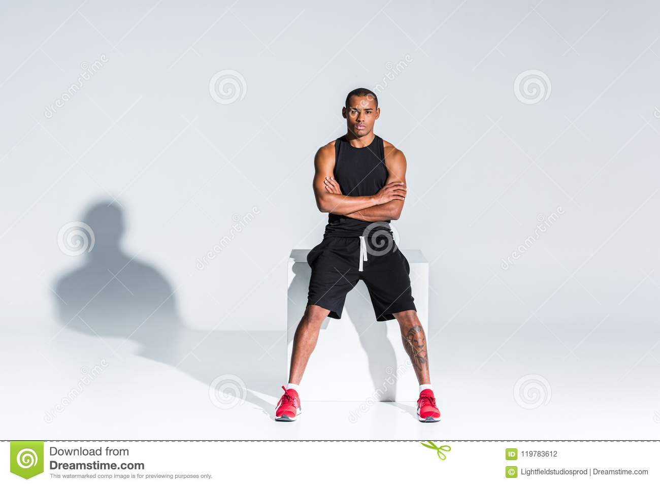 young african american sportsman with crossed arms sitting and looking at camera