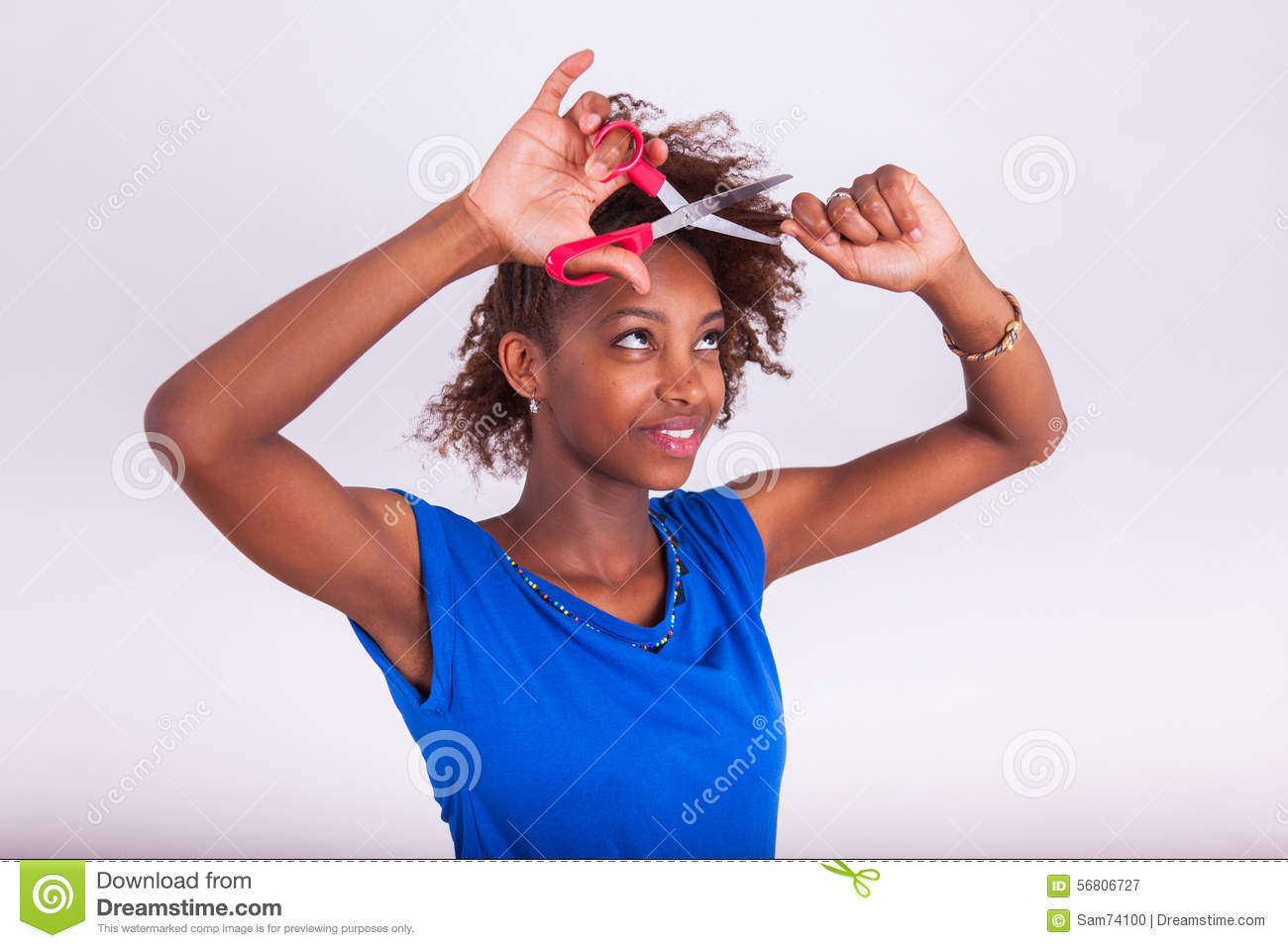 Young African American woman cutting her frizzy afro hair with s