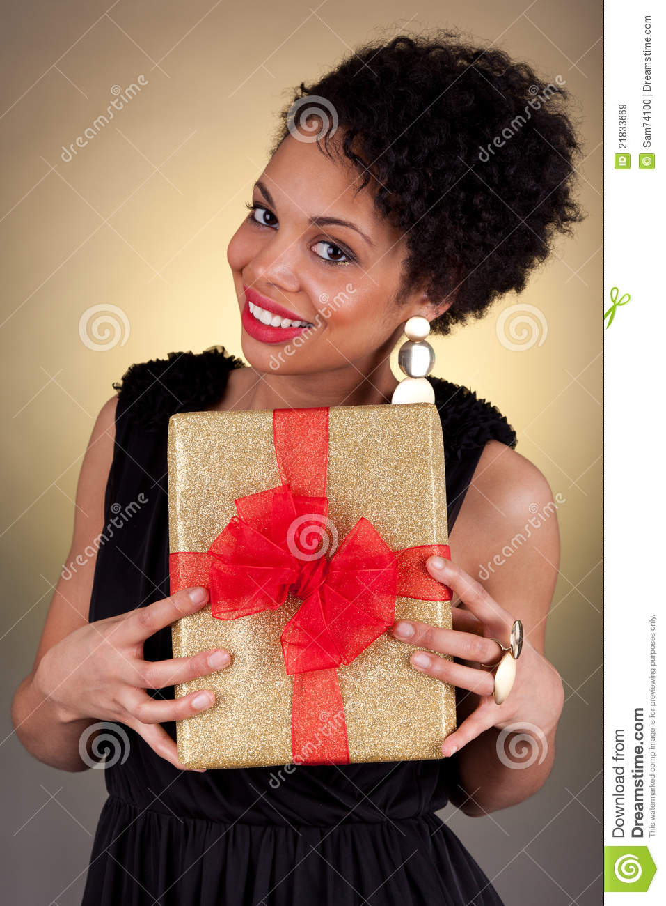Young African American Woman Holding A Gift Royalty Free