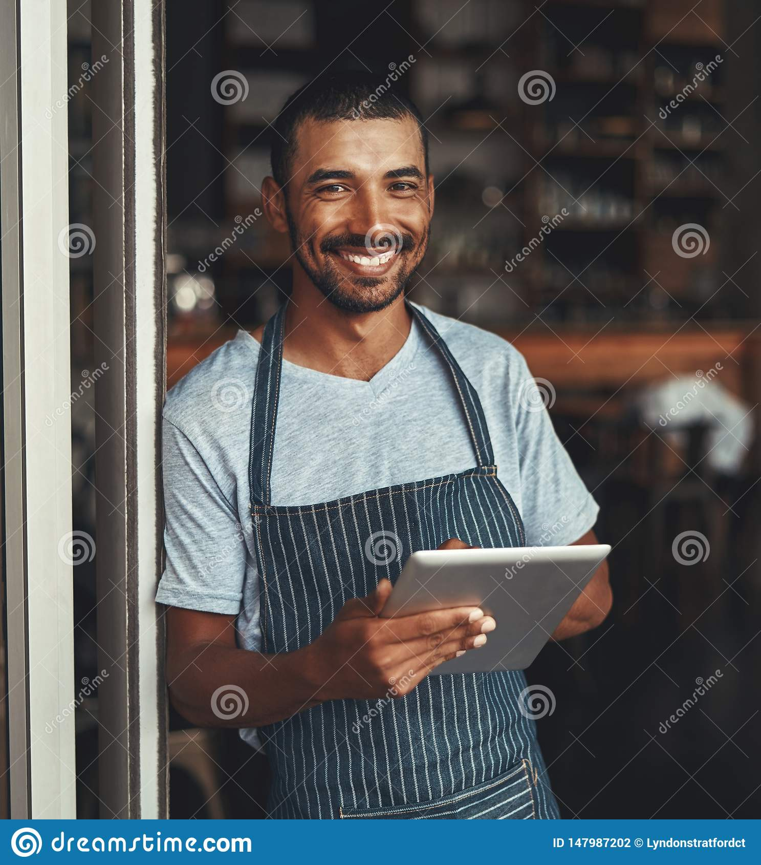 A young african cafe entrepreneur holding digital tablet