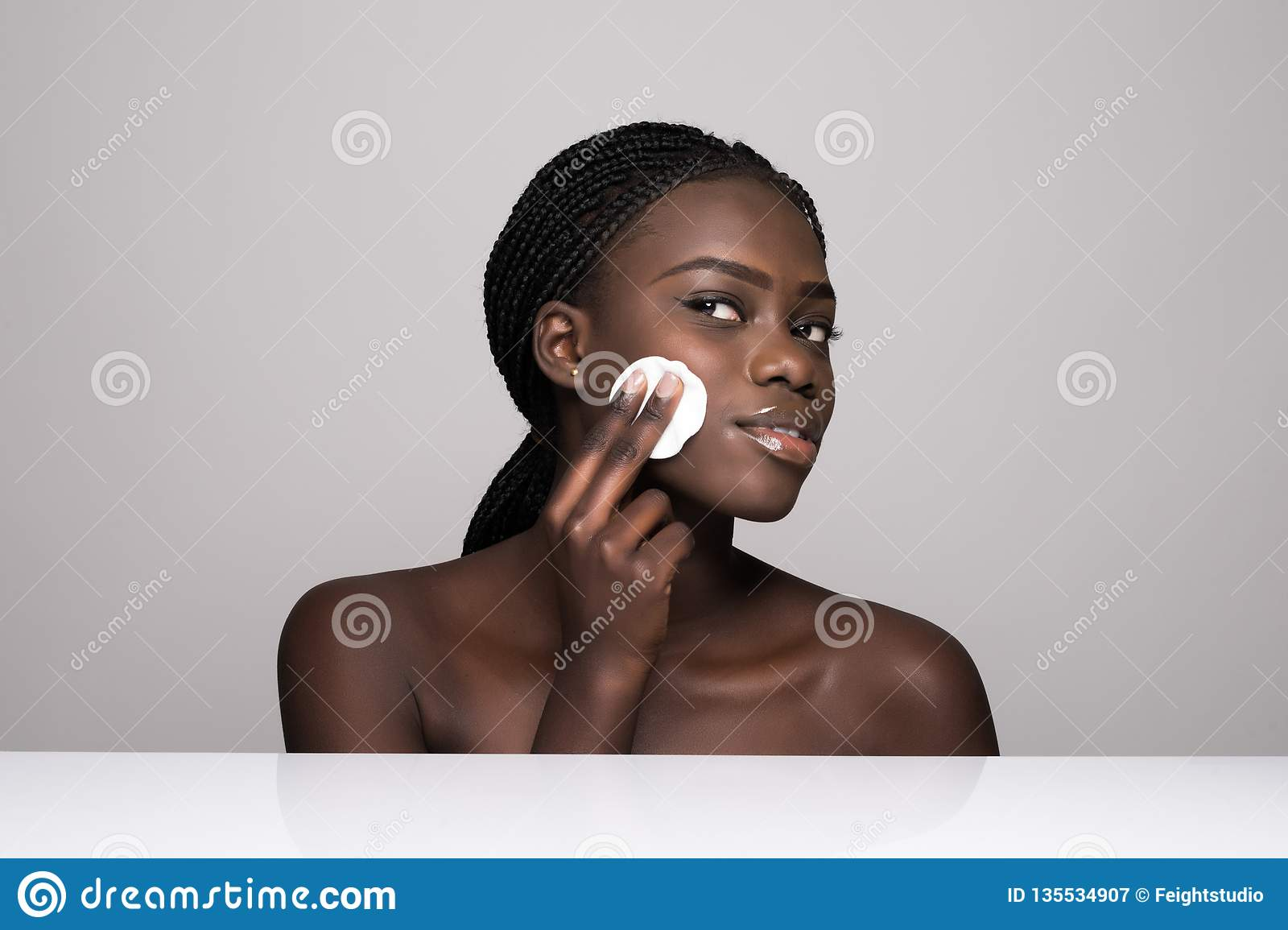Young African Girl Applying Foundation On Her Face Using