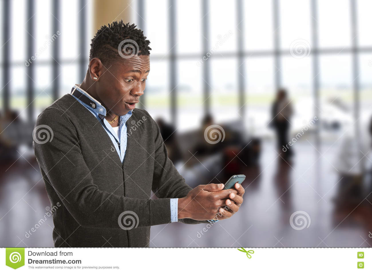 Young african guy looking at cell phone