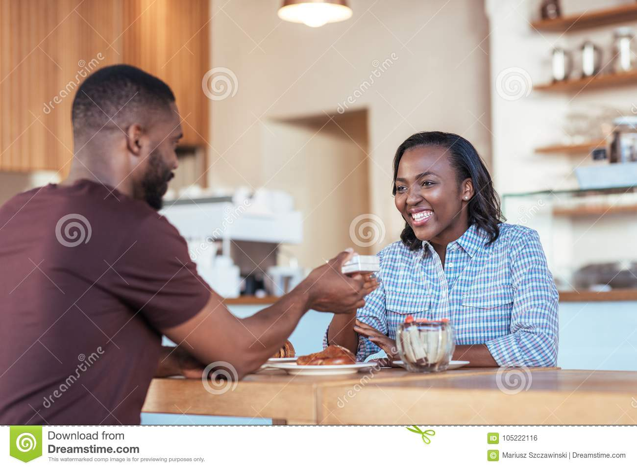 Young African man giving a present to his smiling girlfriend