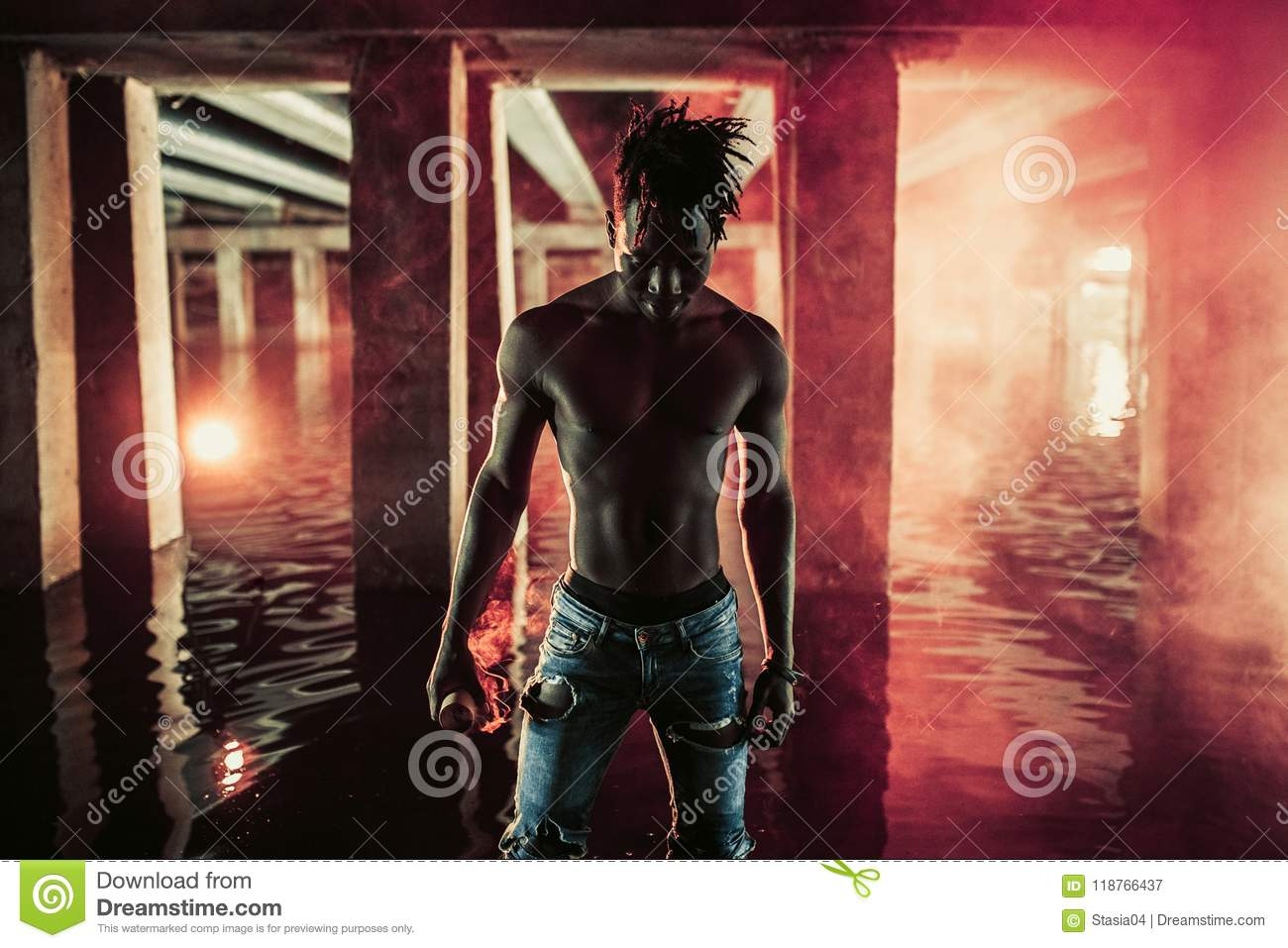 Young African man stands under bridge and holds colored red smoke bomb