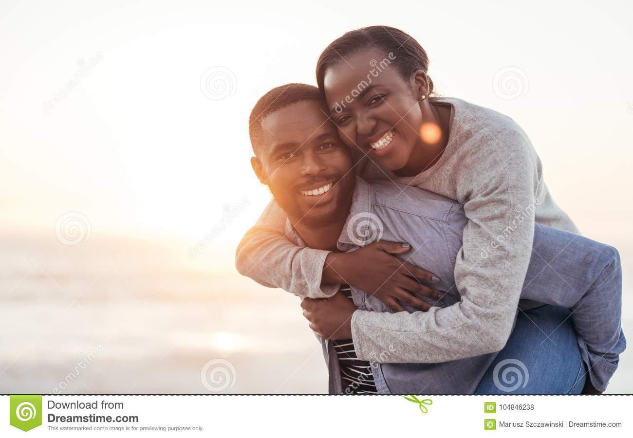 Smiling African couple enjoying a carefree day at the beach