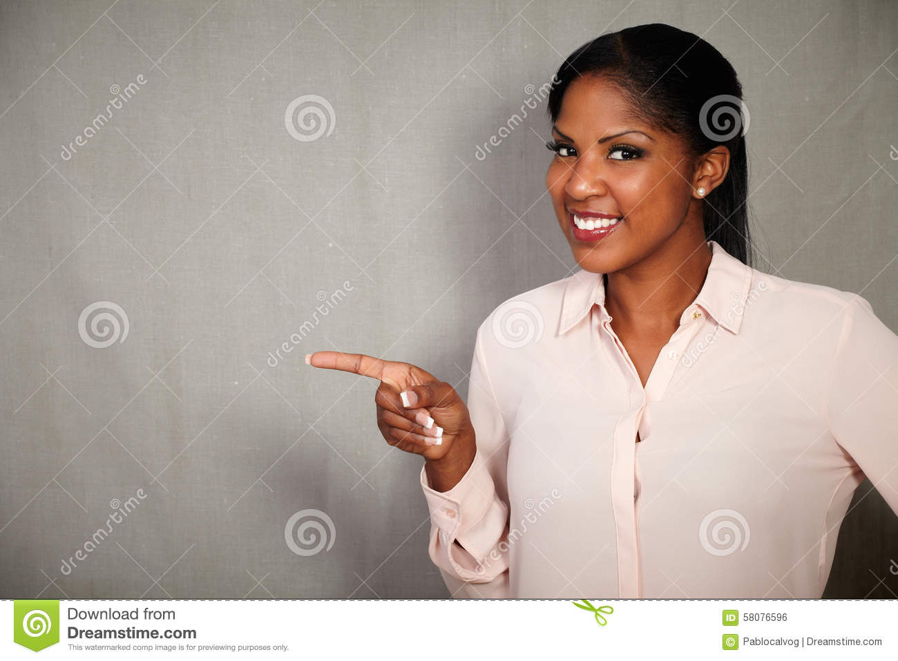 Young african woman pointing while smiling
