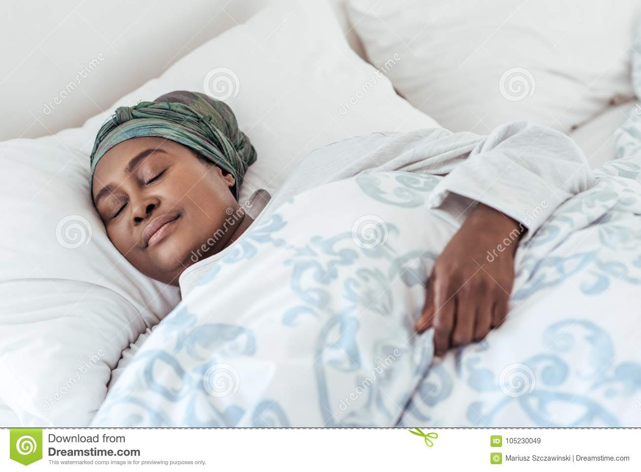 Young African woman lying in her bed fast asleep