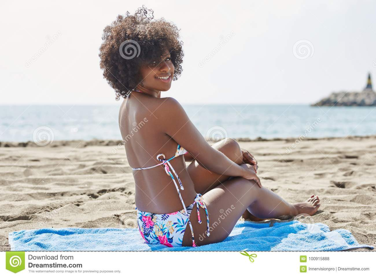 young afro american woman sitting on beach smiling stock photo