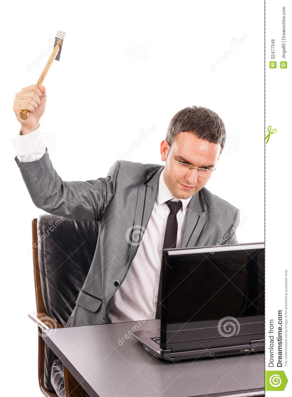 Young angry business man with a hammer smashing a laptop