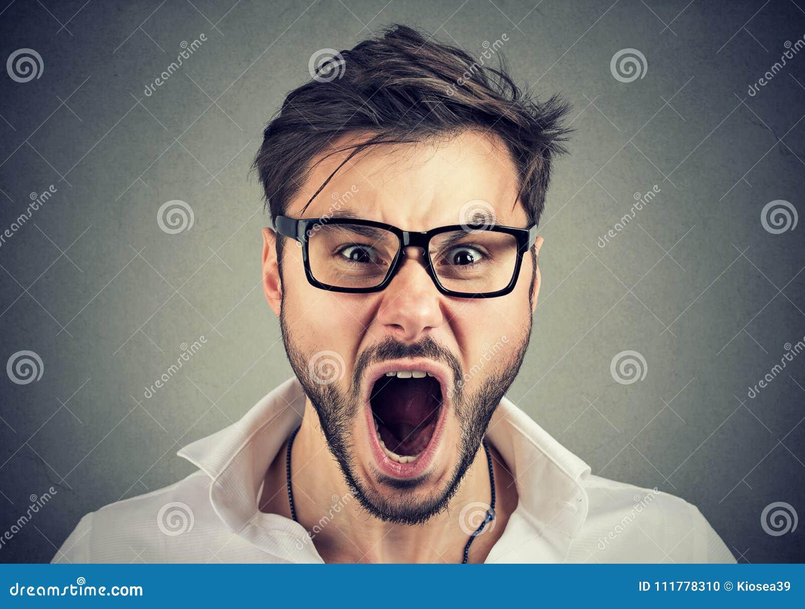 Young angry man looking at camera and screaming