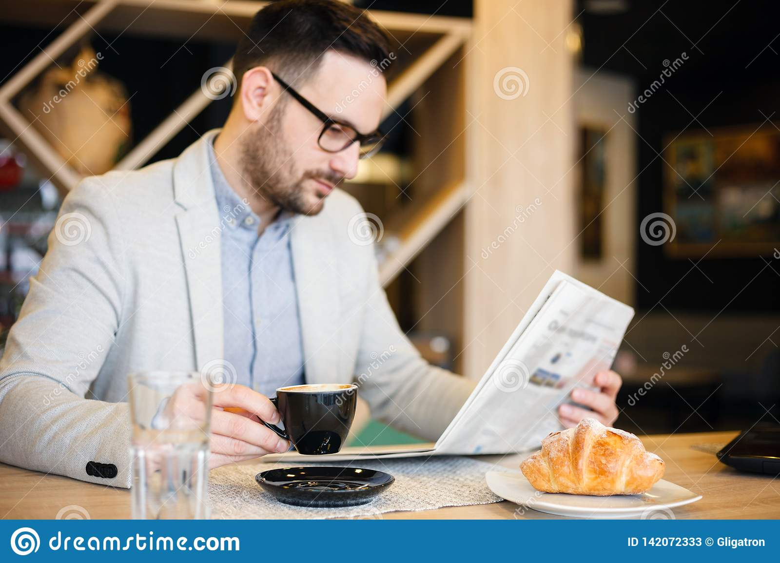 Young architect reading newspapers and drinking coffee in a modern cafe. Work anywhere concept