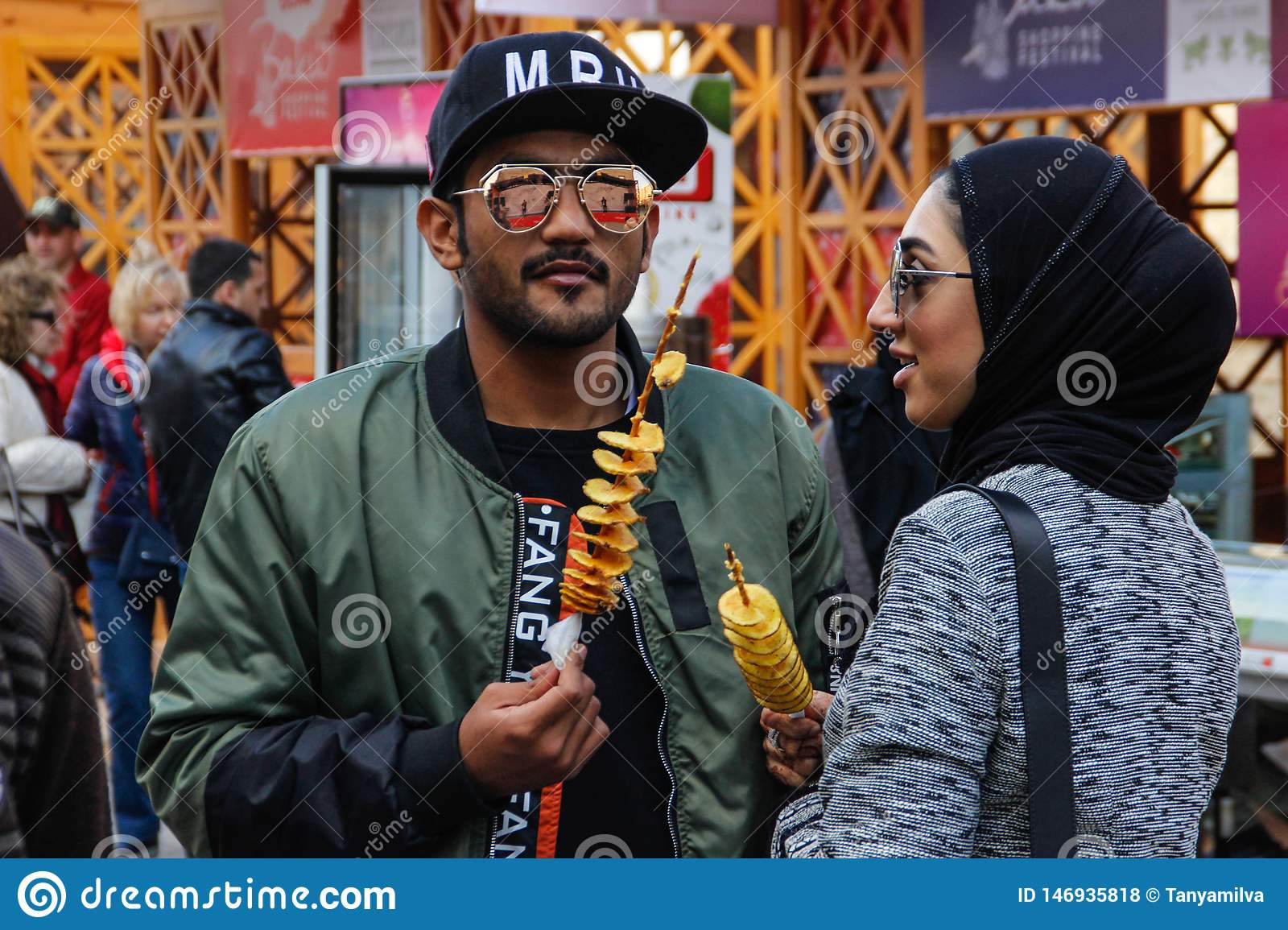 A young Arezbijian couple in hijab and glasses eating potato chips on a stick. Street food of Azerbaijan