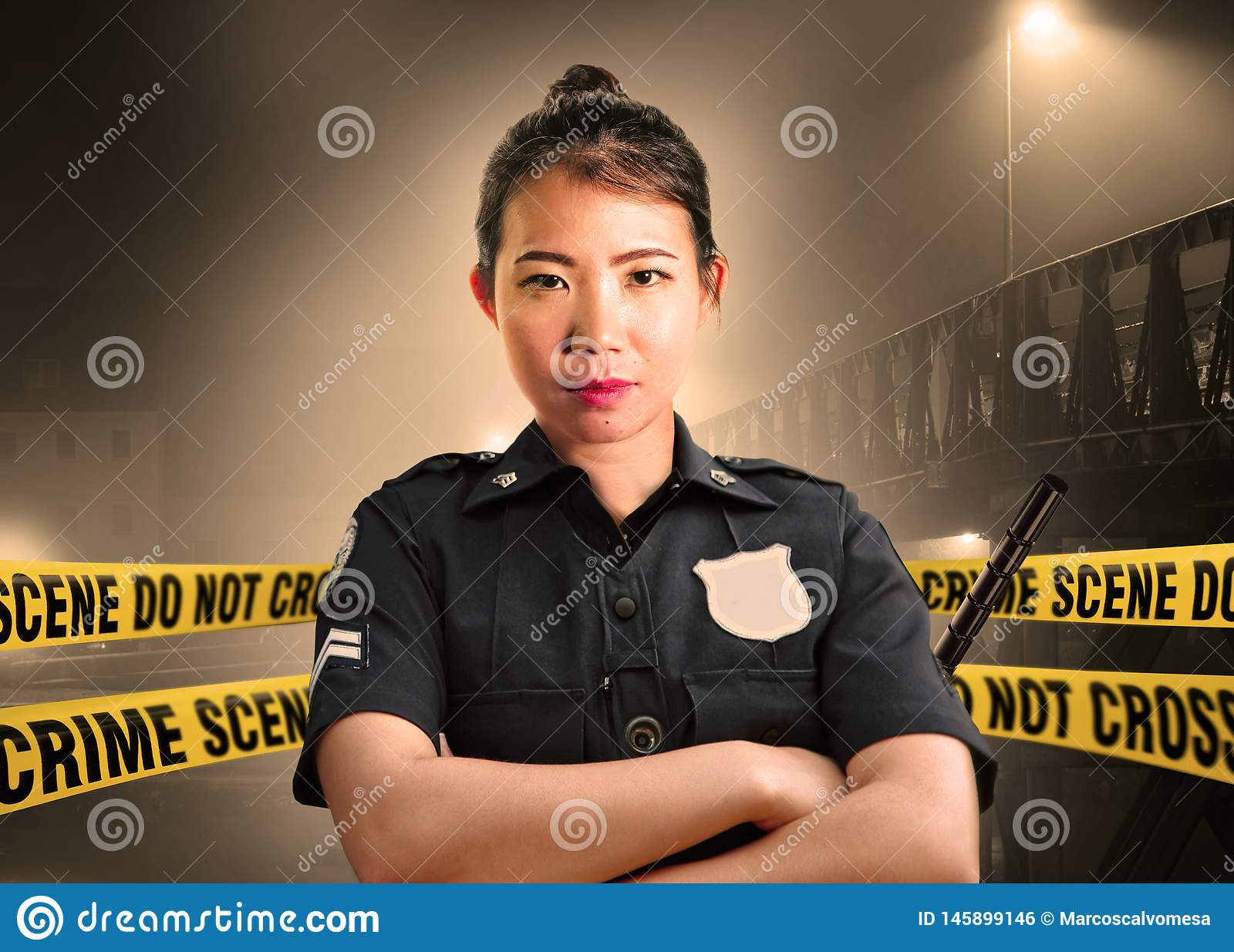 Young Asian American police officer standing serious in custody of crime scene for preserving evidence at do not cross police line