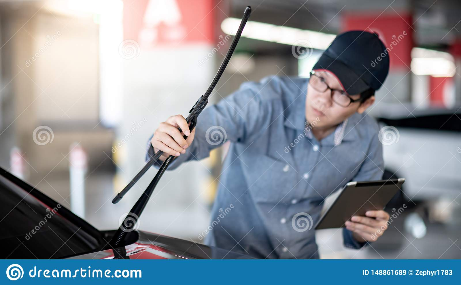 Asian auto mechanic checking windshield wiper