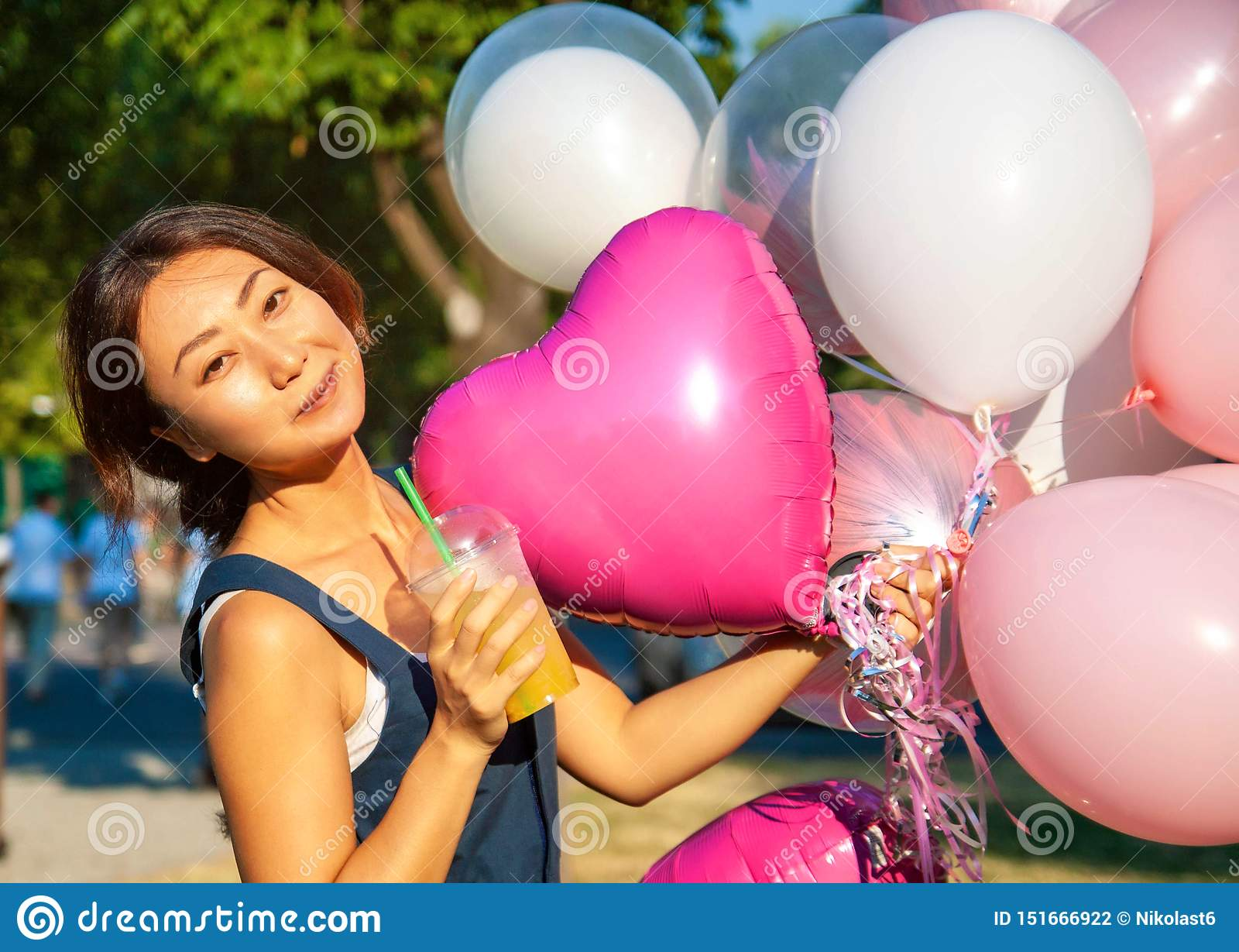 Young asian beautiful woman with flying multicolored balloons in the city.