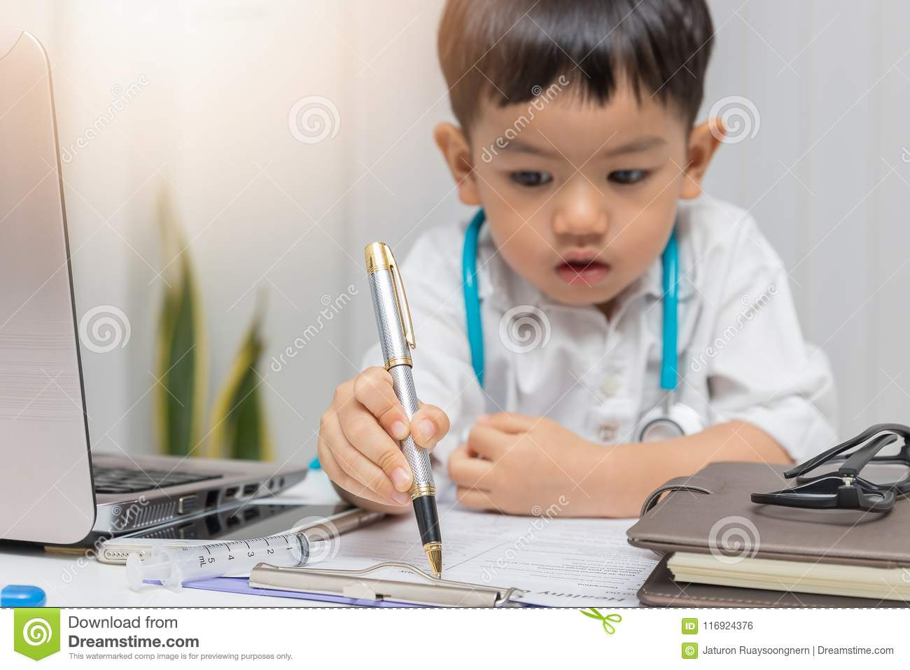Young asian boy playing doctor and writing on diagnostic chart