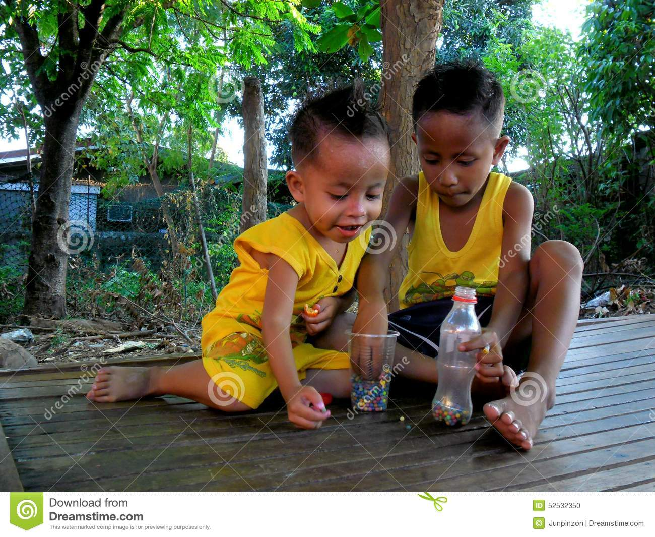 Young asian boys playing under a tree