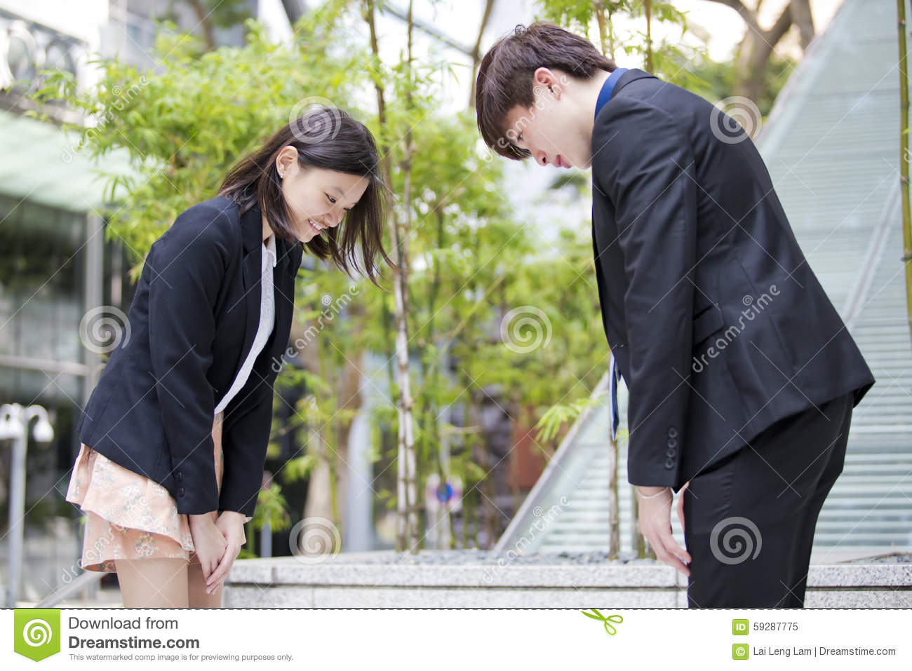 Young Asian business executives bowing to each other