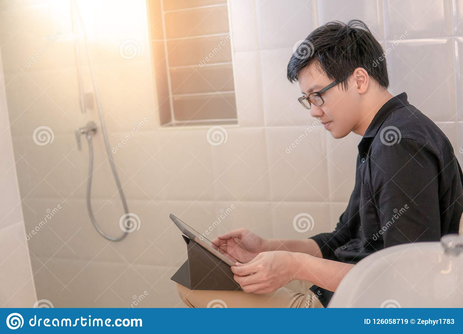 Asian business man using tablet in bathroom