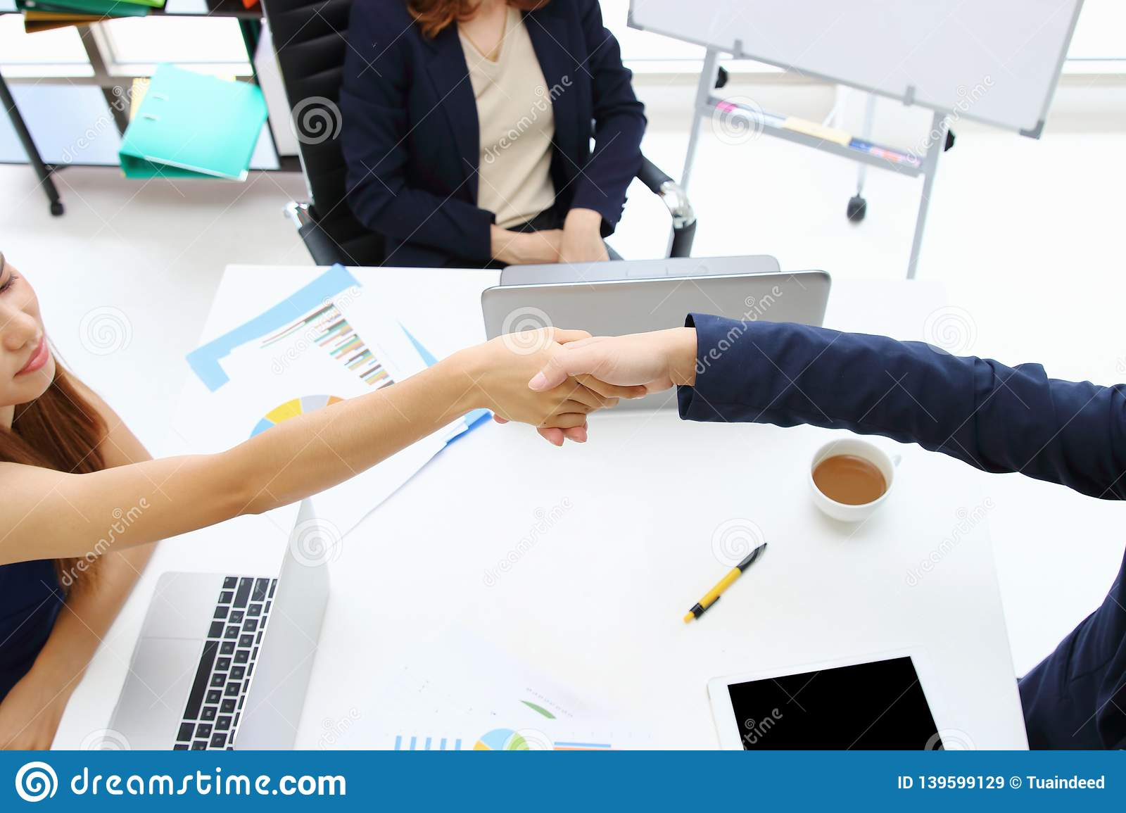 Young Asian business people shaking hands with partners after finishing a meeting. Handshake greeting deal concept