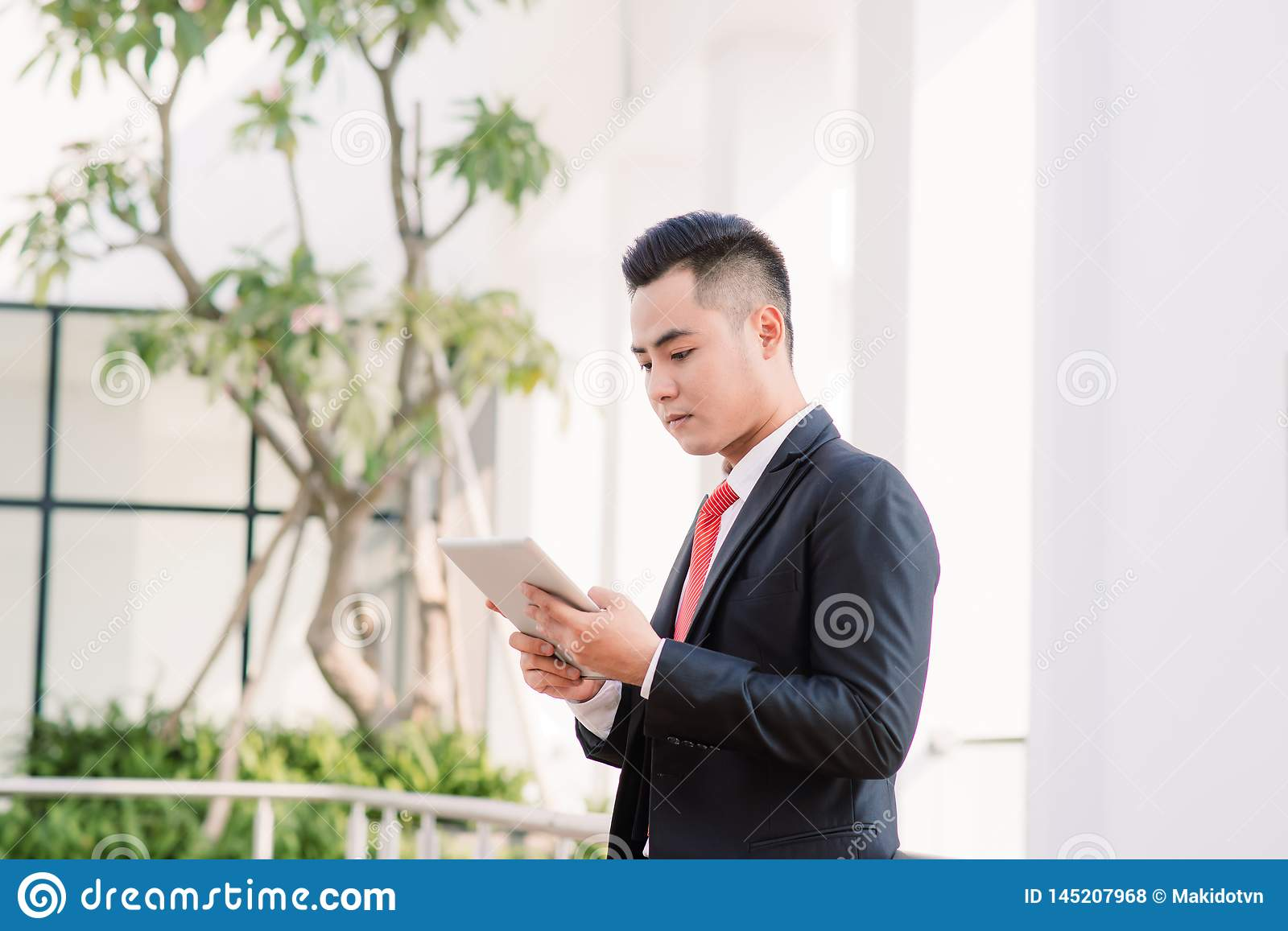 Young Asian Businessman working on tablet, Lifestyle of modern male to communicate, message or use technology in business, Always