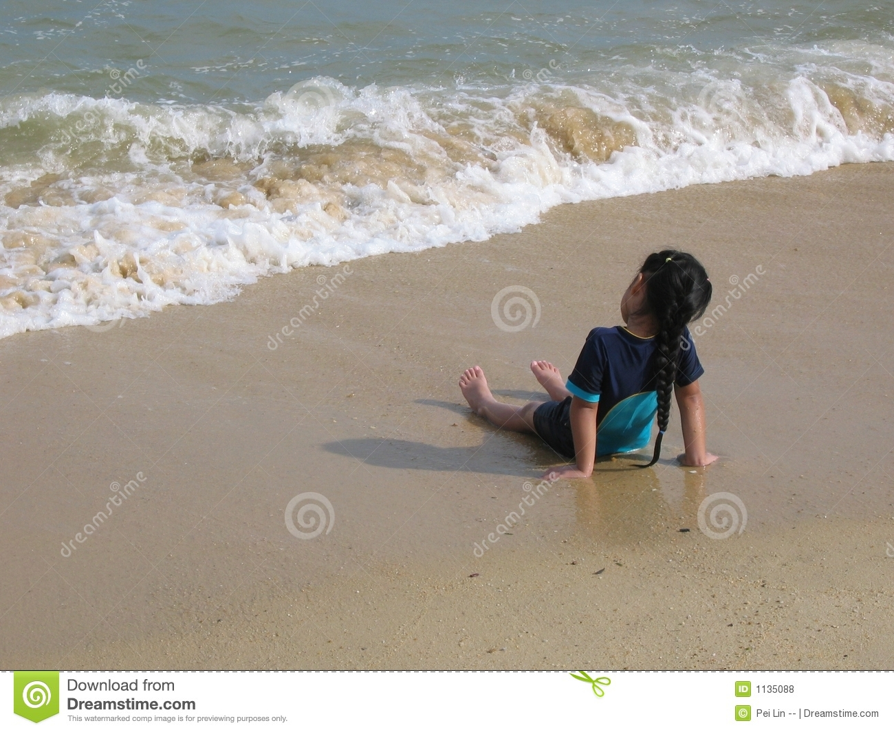 Young asian child, girl staring at the waves on beach