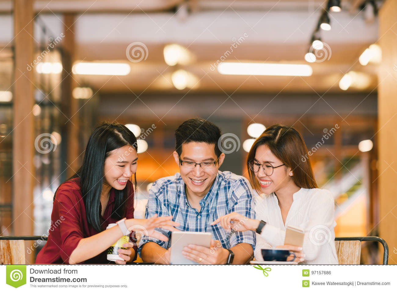 Young Asian college students or coworkers using digital tablet together at coffee shop, diverse group. Casual business, freelance