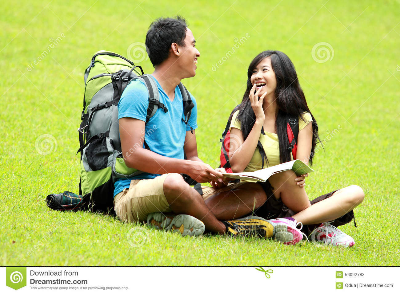Young asian couple chatting and sitting on the grass