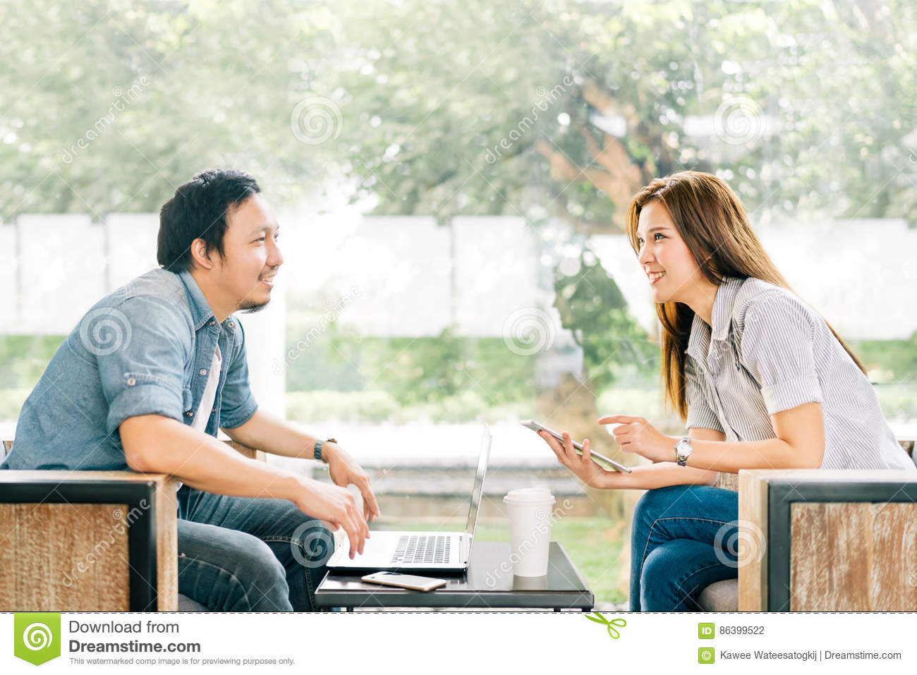 Young Asian couple or coworker talking at coffee shop or modern office