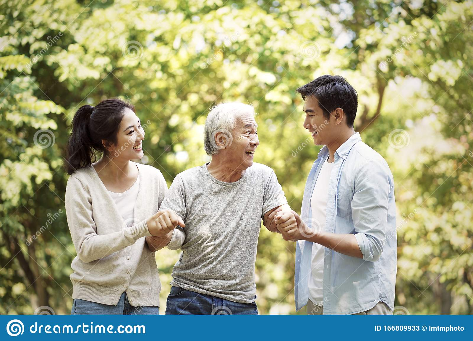 Young Asian Couple Helping Old Man Walk Stock Image