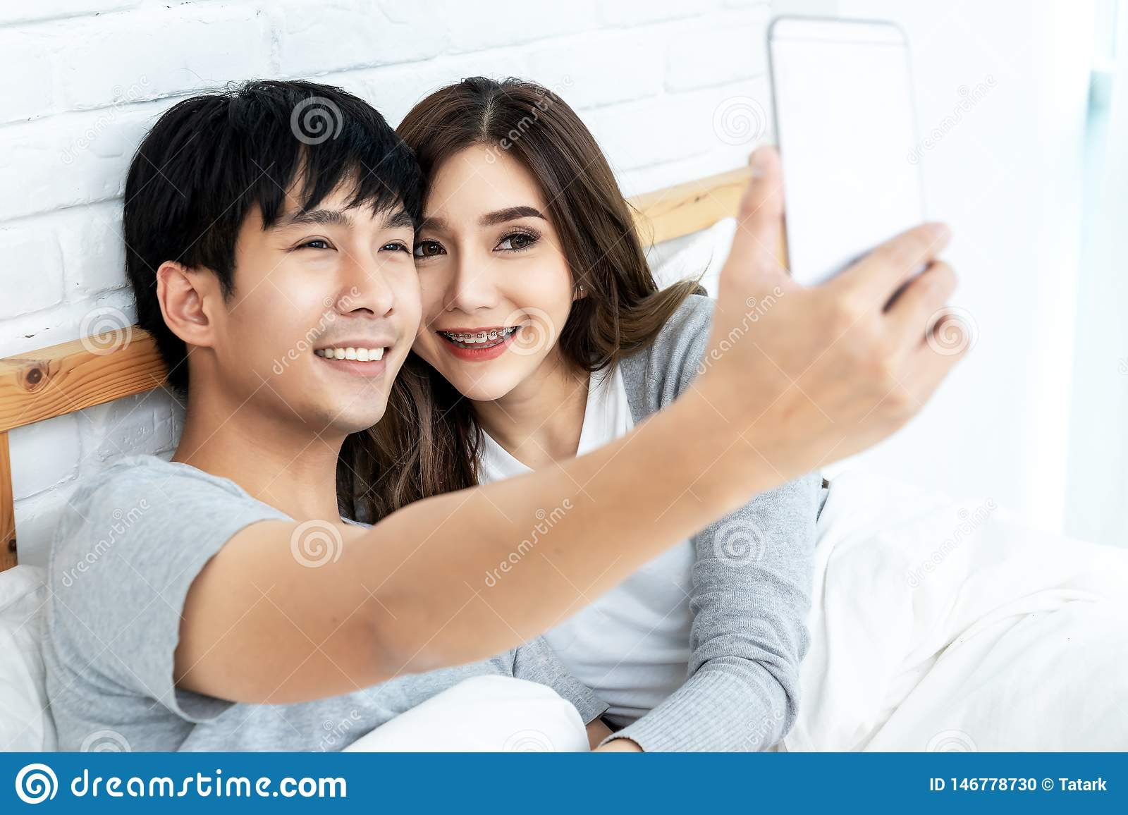 Young asian couple lying on bed and taking selfie by smartphone. Asian lovers take a photo with toothy smile. Happy lover hug each