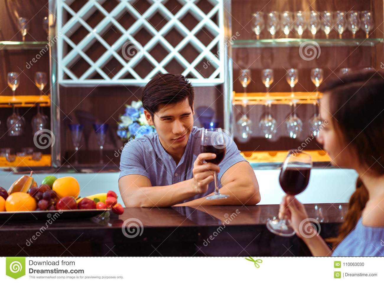 Young asian couple together man and woman clink glasses