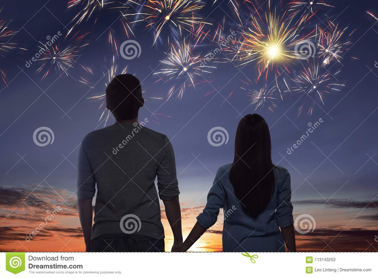 Young asian couple watching spectacular fireworks