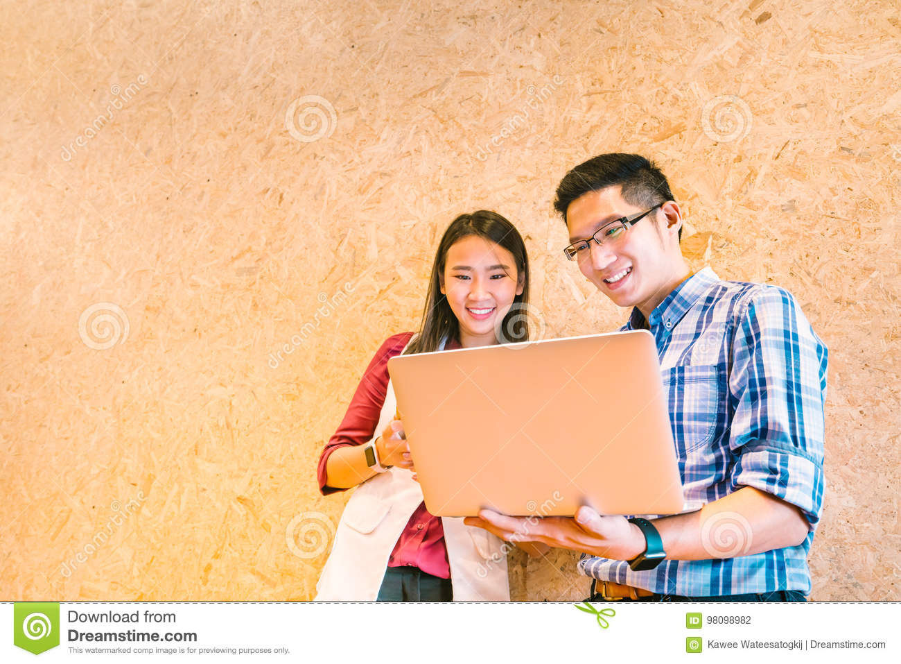 Asian coworker or college student team using laptop computer together at office or campus. Happy casual business talk