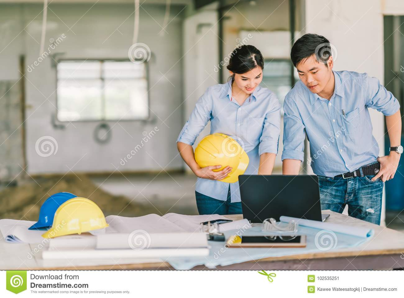 Young Asian engineer couple work together using notebook computer at building construction site. Civil engineering meeting concept