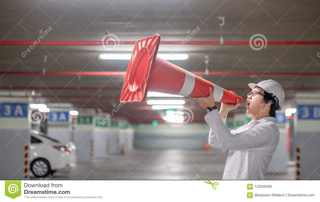 Asian engineer yelling though traffic safety cone in parking lot