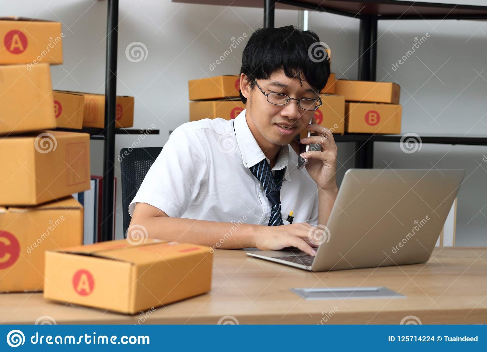 Young Asian entrepreneur owner talking on phone at workplace at home. Start up small business.