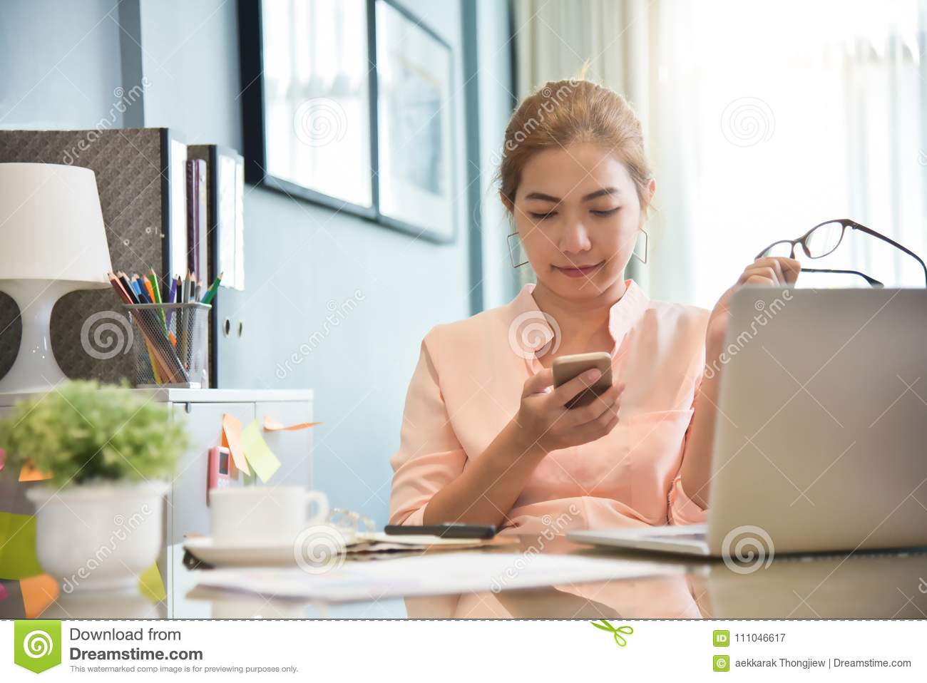 Young Asian Female creative designer using cell phone.