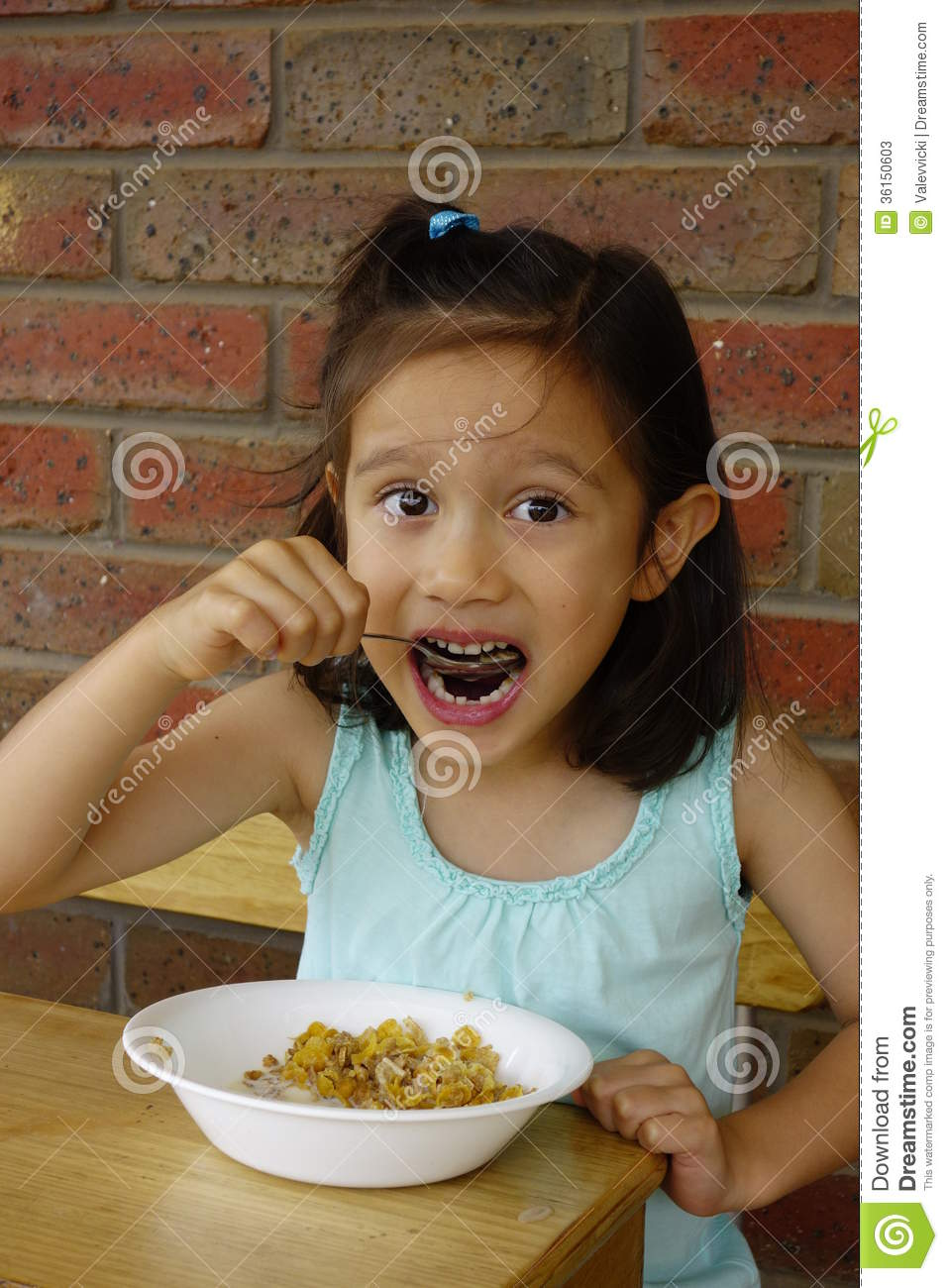 young asian girl eating breakfast cereal stock photos