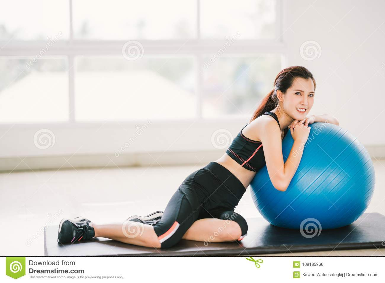 Young Asian girl exercise at clean home gym, sports club. Rest on fitness ball. Yoga aerobic class, sport trainer concept