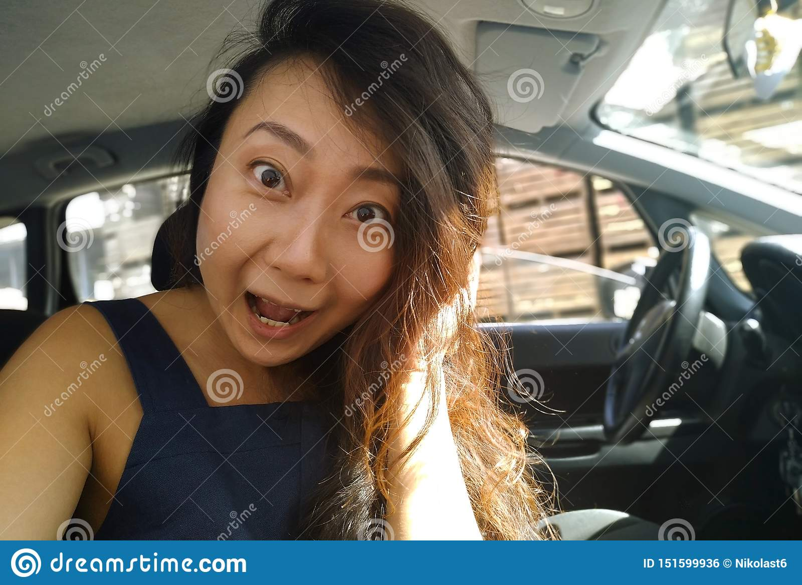 Young asian girl sitting inside of a car and surprised looking at camera.
