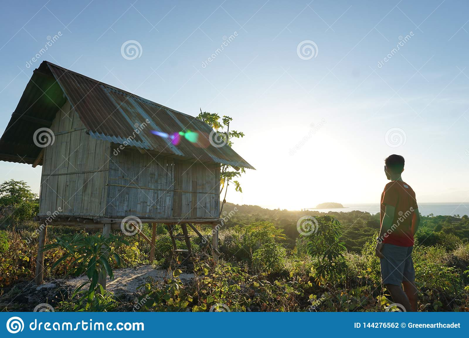 Young man reach to the top of hill then enjoy the sunrise from the top