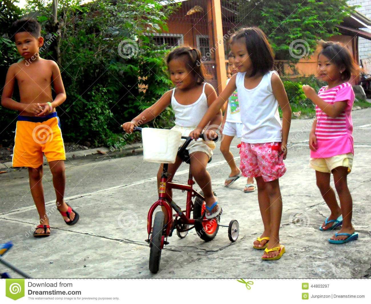 Photo of young asian boys and girls playing in the streets and riding a  bicycle
