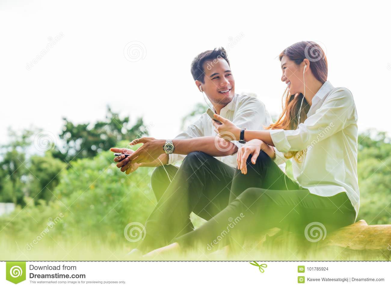 Young Asian lovely couple or college students sit listening to song music on smartphone together in park